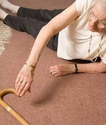elderly woman lying on the floor reaching for her walking stick