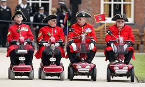 This image shows Chelsea pensioners on mobility scooters