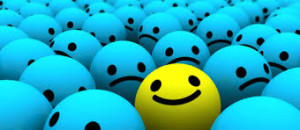 this photo shows a mass of blue balls with sad faces and one yellow happy one !