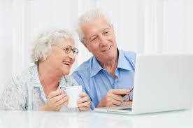 this image shows and elderly woman with a younger man looking at the screen of a laptop.