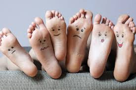 This image shows 4 feet with faces on the soles !