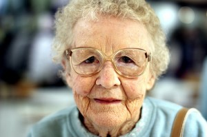 elderly lady with a wrinkled face and glasses not smiling