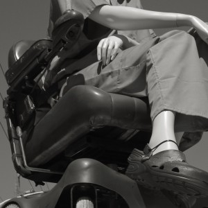 black and white picture of a dummy/model sat on a mobility scooter