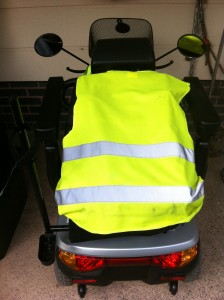 this image shows a mobility scooter which is highly visible due to a vest