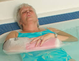 this image shows an older lady in a pool with a waterproof cover on