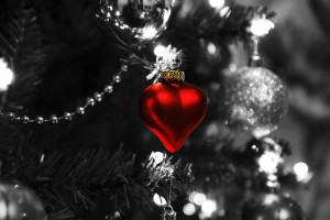 a black and white photo of a Christmas tree with a lovely metalic heart in red