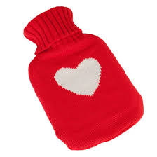 this image shows a hot water bottle in a knitted red case with a heart in white in the centre
