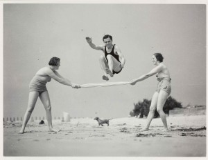 a black and white photo of 2 women and a man exercising on a beach