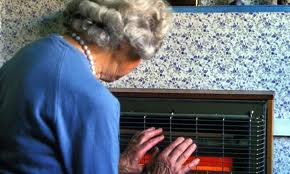 An elderly woman warming her hands in front of an electric fire
