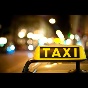 a yellow taxi sign with the word taxi in black print