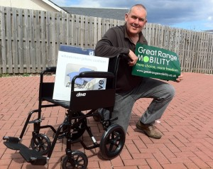 Iain McLarty with the wheelchair he kindly donated to an elderly african woman in need