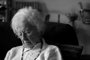 a black and white photo of an elderly woman asleep in a chair