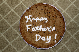 "a fruit cake with the words in white icing ""Happy Fathers Day"""