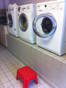 a row of washing machines raised on a plinth in a communal laundry and a red plastic stool.