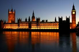 a picture of the houses of parliament lit up at night