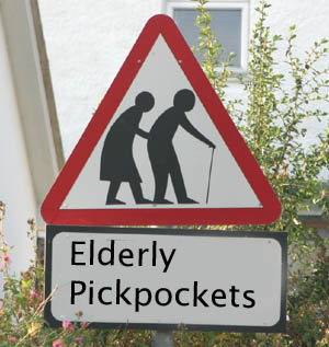 a red triangle road sign with a elderly man and woman in it . underneath it reads elderly pickpockets