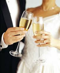a bride and groom with champagne glasses in hand