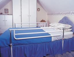 a bedroom scene showing a single bed with blue bedding and white cot sides