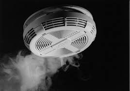 a white smoke detector against a black background showing some smoke nearlby
