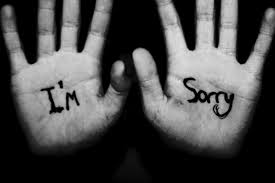 "a black background with two hands one with ""I'm"" the other with ""sorry"" on."