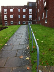 a picture of a red brick block of flats with a steep path and hand rails leading to them