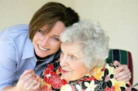 this image shows an elderly lady with a younger dark haired female carer