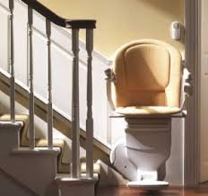This image shows a white staircase with railings and a stairlift at the bottom