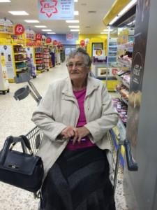 this shows and elderly woman in a specially adapted shopping trolley
