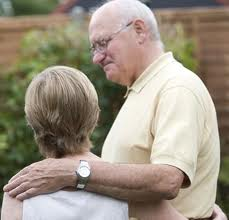 this image shows a tall elderly man with his hand on a woman's shoulder
