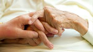 a young hand holding an elderly one