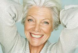 this shows a female with grey hair smiling with her hands behind her head.