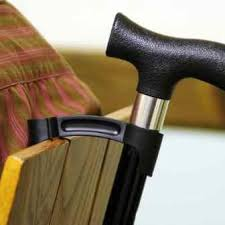 this image shows a walking stick and crutch holding clip,it fixes to the walking aid and can be hooked onto the back of chairs / counter tops etc