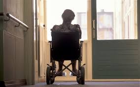 this image shows an elderly person alone in  wheelchair at the end of a hospital corridor.