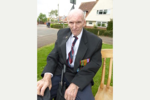 this is a photo of an elderly gentleman wearing his medals with pride