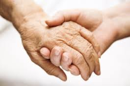 this image shows two people holding hands one elderly and one younger.