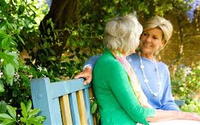 this image shows an elderly woman talking to another younger woman sat on a blue bench