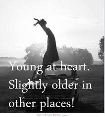"""this image shows a female stood on the bonnet of her car and the words """" Young at heart slightly older in other places !"""""""