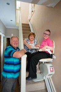 This image shows a disabled boy using an acorn stairlift which was kindly dontated