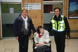 this image shows 3 women. one police officer and a woman in a wheelchair