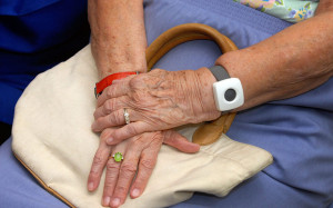 This image shows and elderly person wearing a wrist call bell and crossed hands