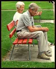 this image shows an elderly couple sat on a park bench