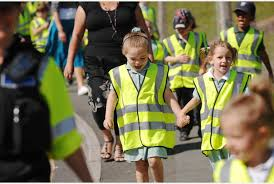 this image shows school children wearing high visibility vests