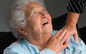 this image shows an elderly lady looking up to her carer whilst touching her hand.