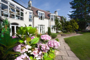 This image shows an award winning care home in Manchester. Dystlegh Grange, is housed in a former golf club house.