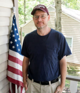 this image shows a man in his 40's.He has a baseball cap on, trousers/pants and a blue tee shirt. He is stood on a veranda in the US