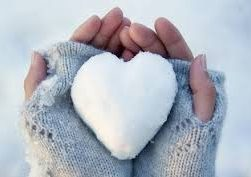 this image shows a heart made from snow held in soft pale grey fingerless gloves