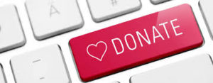 this image shows a donate button on a key board. The button is pink and has a heart on it.