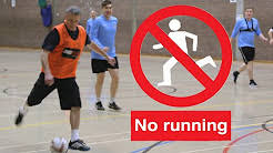 this image shows an indoor football game and a red circle with a running man inside and a sign saying no running