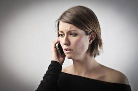 this image shows a young lady on her mobile looking worried