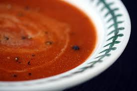 this image shows a white bowl containing tomato soup